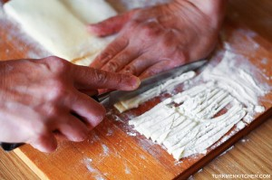Using a sharp knife, cut the folded dough into thin noodles.