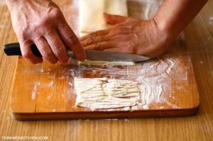 Bir eliňi hamyryň üstünde goýup, hamyry pyçak bilen inçejik kesmeli.